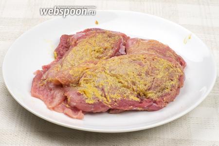 Свинину  вымыть и просушить, затем нарезать ломтиками толщиной приблизительно 1 см, немного отбить, обильно смазать 5-6 ложками  горчицы, накрыть пищевой плёнкой и поставить в холодильник на 40-50 минут.