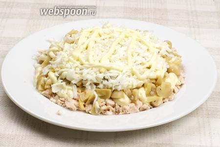 Затем выложить слой белков, на белки выложить слой тёртого сыра и всё смазать майонезом.