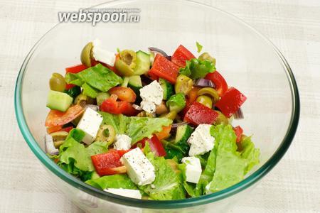 Все продукты осторожно перемешать, заправить оливковым маслом, выложить на листья салата и сверху на перемешанный греческий салат выложить сыр Фета, и добавить свежемолотый чёрный перец.