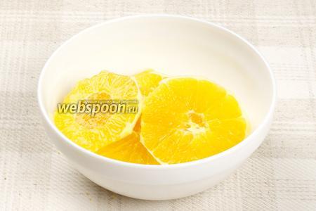 С двух апельсинов счистить кожуру и порезать на кружочки толщиной в 1-2 см.