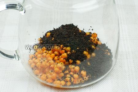 В чайник всыпать облепиховое пюре, оставшиеся ягоды и чёрный чай.