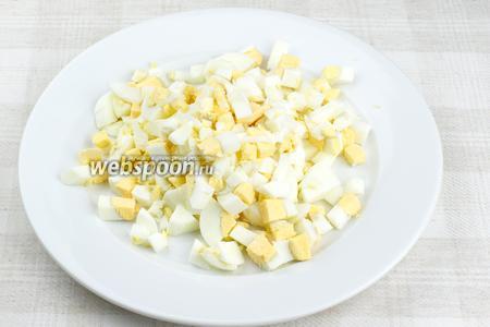 Яйца предварительно отварить вкрутую (опустить в холодную воду, довести до кипения и варить 10 минут с момента закипания), а затем порезать кубиками, оставив 1 желток.