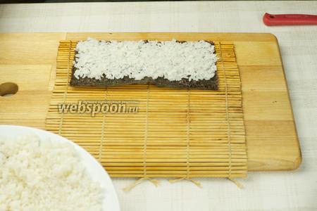 Листы нори разрезать пополам. На макису положить нори, а затем на него выложить рис тонким слоем 0,5-0,8 см, так чтобы дальний край от вас не был покрыт рисом на 1-1,5 см (это необходимо чтобы лист склеился в ролл).