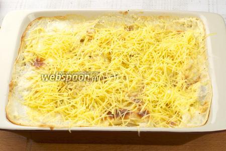 Когда картофель уже мягок, достать форму и обильно присыпать тёртым сыром.