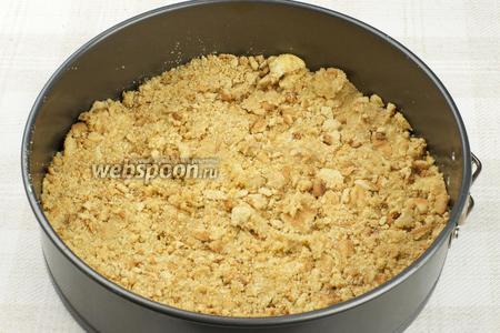 Разъёмную форму для выпекания смазать сливочным маслом и выложить массу из крошек.