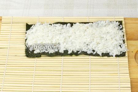 Листы нори разрезать пополам.  Распределить рис на половине нори равномерным слоем толщиной приблизительно 1 см.