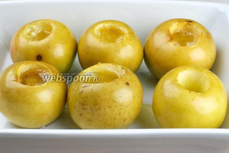 Выпекать в разогретой до 180 °С духовке 10-20 минут, пока не начнёт лопаться кожица яблок. Подавать с изюмом и грецкими орехами.