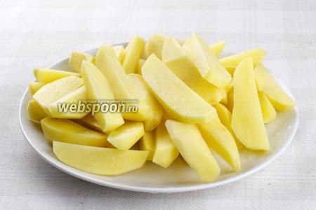 Картофель очистить, хорошо помыть и порезать вдоль широкими кусками.