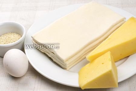 Для приготовления пирога возьмём готовое слоёное тесто, твёрдый сыр двух сортов, яйцо и несколько ложек семян кунжута.