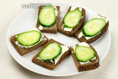 Ломтики хлеба тонко смазать сливочным маслом и сверху положить по кружочку огурца.