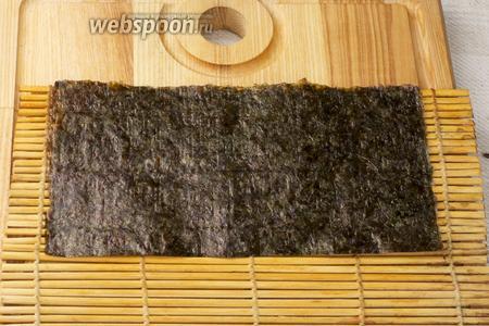 Половину одного листа нори выложить на бамбуковый коврик.