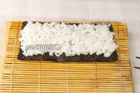 На макису положить половину листа нори, а сверху равномерно распределить рис толщиной 1-1,5 см.
