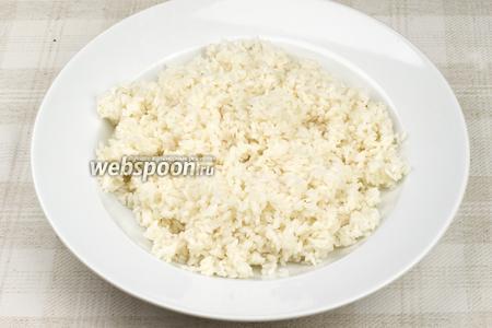 После того, как рис настоялся, высыпаем его на ровную поверхность или тарелку, добавляем заправку в горячий рис и хорошо перемешиваем палочками. После рису необходимо дать немного остыть.