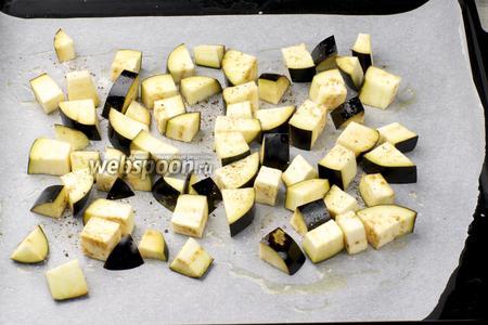 Противень застелить пергаментной бумагой, сбрызнуть растительным маслом, выложить порезанные баклажаны, посолить  поперчить.