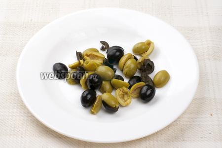 Оливки и маслины разрезать на половинки.