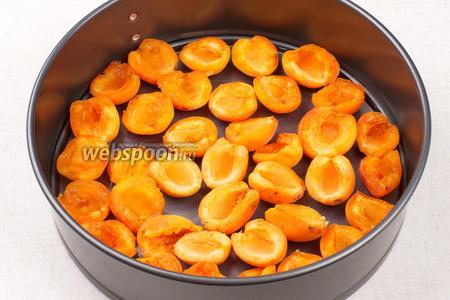 Форму для выпекания смазать сливочным маслом и выложить половинки абрикос.