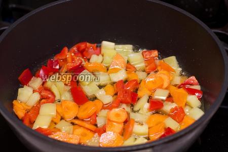 В отдельной сковороде разогреть 2 ст.л. растительного масла и обжарить перец с морковью 2-3 минуты.