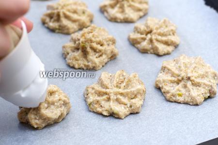 Застелить противень пергаментной бумагой и смазать сливочным маслом.   Затем выложить тесто ложкой или с помощью кулинарного мешка. Получается приблизительно 15 штук.