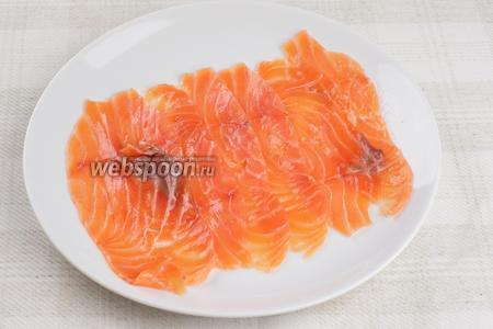 На плоское блюдо выложить ломтики рыбы в один слой.