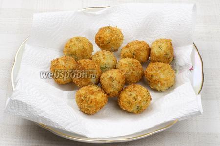 Крокеты вынимайте на бумажное полотенце, чтобы удалить лишний жир.  Готовые крокеты остудить, подавать на тарелке украшенной листьями салата.