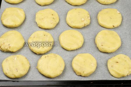 Застелить противень пергаментной бумагой и  сформировать из теста печенье — сначала скатать шарик величиной с куриное яйцо, а затем сделать из него лепёшку. Выкладывать печенье друг от друга на расстоянии 2 см, получается 16-20 штук.