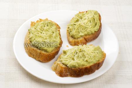 Выложить приготовленную начинку на поджаренный хлеб и присыпать всё пармезаном.
