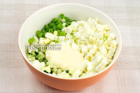 Соединить мясо криля, яйца, огурец, мелко порезанный зелёный лук и 1-2 столовые ложки майонеза.