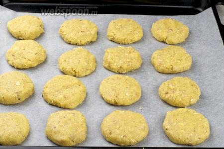 Застелить противень пергаментной бумагой и руками сформировать печенье, выкладывать печенье на расстоянии  1-2 см друг от друга.