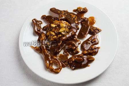 На другую подготовленную тарелку, смазанную маслом, вылить карамельную смесь с орехами тонким слоем, полосками (как будет получаться).