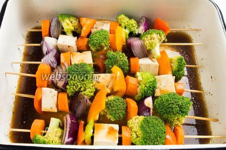 На влажные шпажки аккуратно (сыр очень нежный) нанизать все ингредиенты так, чтобы получился красивый цветной ряд из овощей и сыра. Сложить шашлык в удобную посуду и залить маринадом. Поставить в холодильник на 1 час. Периодически переворачивать шашлык в маринаде.