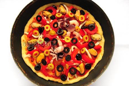 Присыпьте нарезанными оливками и маслинами.