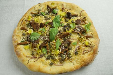 Поставить в горячую духовку 240 ºC. Выпекать в течение 15 минут. Готовую пиццу украсить мелкими листьями базилика. Подавать к столу горячей.