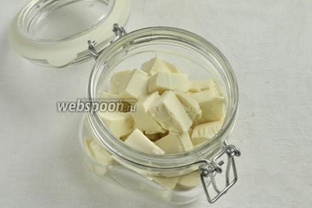 Сложить кубики сыра в стеклянную банку.