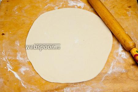 После того, как тесто поднялось, притрусить стол мукой и раскатать тесто скалкой в направлении от середины к краям. Несколько раз подбросить в воздухе, хлопая ладонями в середину коржа. Тем самым вы добавите игривости процессу, а пицца будет тонкая в середине, а по краям с пышными бортиками, что поможет начинке не вытечь.