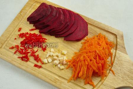 Подготовить овощи: вымыть, почистить. Свёклу нарезать полукольцами. Морковь нашинковать крупно на тёрке. Чеснок нарубить мелко. Перец тщательно очистить от семян, срезать перегородки, вымыть под холодной водой, нарезать мелко.