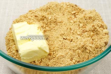 Печенье измельчить в мелкую крошку руками или в блендере и добавить размягчённое сливочное масло.