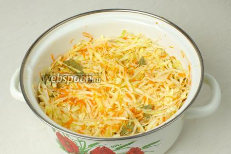 Маленькими порциями утрамбуйте капусту в стеклянную или эмалированную ёмкость. Капуста должна пустить сок, для этого прямо кулаком вдавливайте капусту, насколько хватит сил.