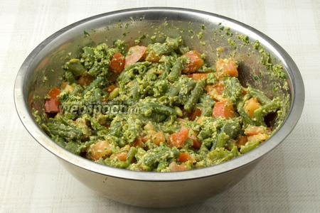 В глубокой миске соедините фасоль, помидоры и измельчённую пасту. Заправьте салат растительным маслом, посолите, поперчите и перемешайте. Дайте салату настоятся 3-5 минут и подавайте к столу тёплым.