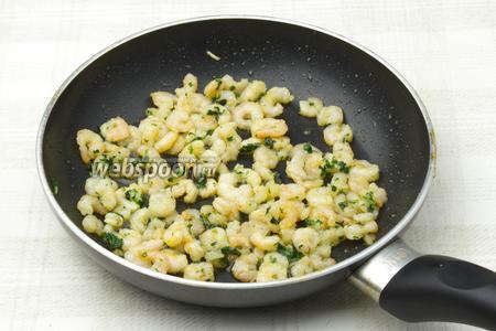 В разогретую сковороду добавьте 3 столовых ложки оливкового масла и обжаривайте на нём креветки с горстью петрушки и выдавленным чесноком 5 минут.