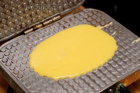 Хорошо разогреть вафельницу и вылить 1-2 столовые ложки теста на ее внутреннюю поверхность.