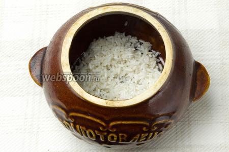 Дно горшочка смазать оливковым маслом и выложить слой риса.