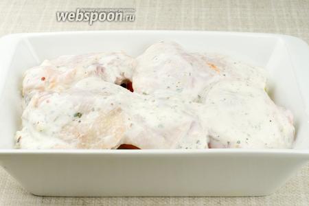 Затем на помидоры уложить куриные бёдра и всё залить маринадом из кефира.