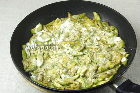 Залить кабачки сметаной и выдавить 2-3 зубчика чеснока. Накрыть крышкой, убавить огонь до минимума и тушить 10-15 минут.  Если сметана густая — добавить небольшое количество кипячёной воды.