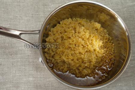 Промыть булгур в проточной воде и всыпать в кастрюлю к чесноку с маслом. Хорошо перемешать, чтобы крупа стала промасленной.