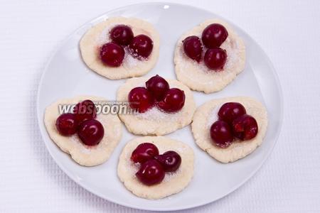 Потом кладём на каждый кружочек 0,5 ч. л. сахара и по 2-3 вишни.