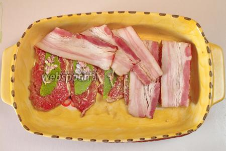 Каждый кусок обернуть беконом, разложив на мясо листья и цветы шалфея.