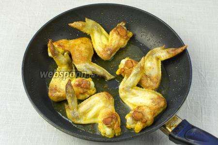 В сковороде хорошенько разогреть масло и выложить крылья. Обжарить с одной стороны до золотистой корочки.