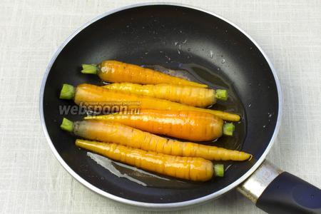 В сковороду выложить морковь и аккуратно перемешать, чтобы морковь равномерно покрылась глазурью. Готовить на слабом огне 2 минуты.
