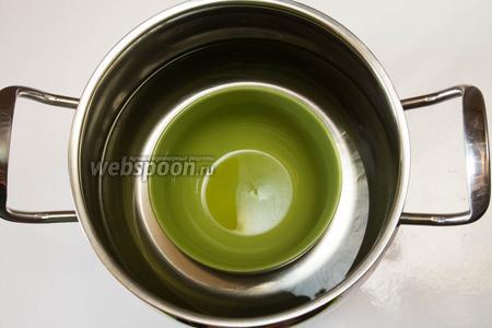 Приготовить кастрюлю с толстым дном, поставить в неё пиалу (стенки смазать оливковым маслом) и залить водой так, чтобы она достигала лишь половины пиалы. Поставить на медленный огонь.