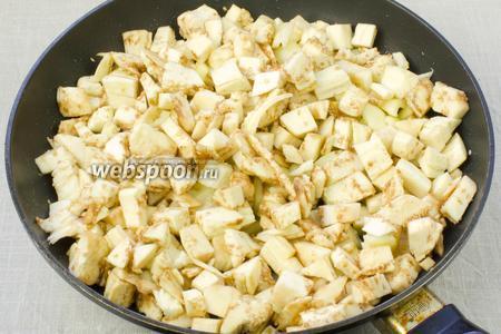 К луку добавить мякоть баклажан и перец. Посолить, поперчить и обжаривать ещё 3 минуты.